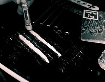 Líneas de cocaína en una mesa con un billete enrollado que se usa para inhalarlas.