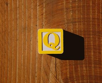 """Bloque de letras de un niño amarillo con la letra """"Q"""" en eso."""