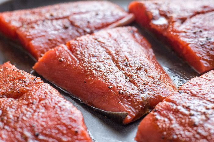 salmón cortado en secciones para receta de salmón a la parrilla con salsa de melocotón y pepino