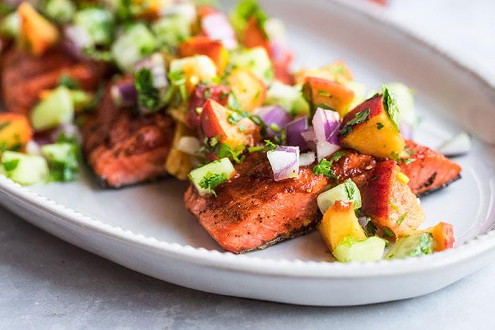 Receta de salmón a la parrilla terminado con salsa de melocotón y pepino en un plato